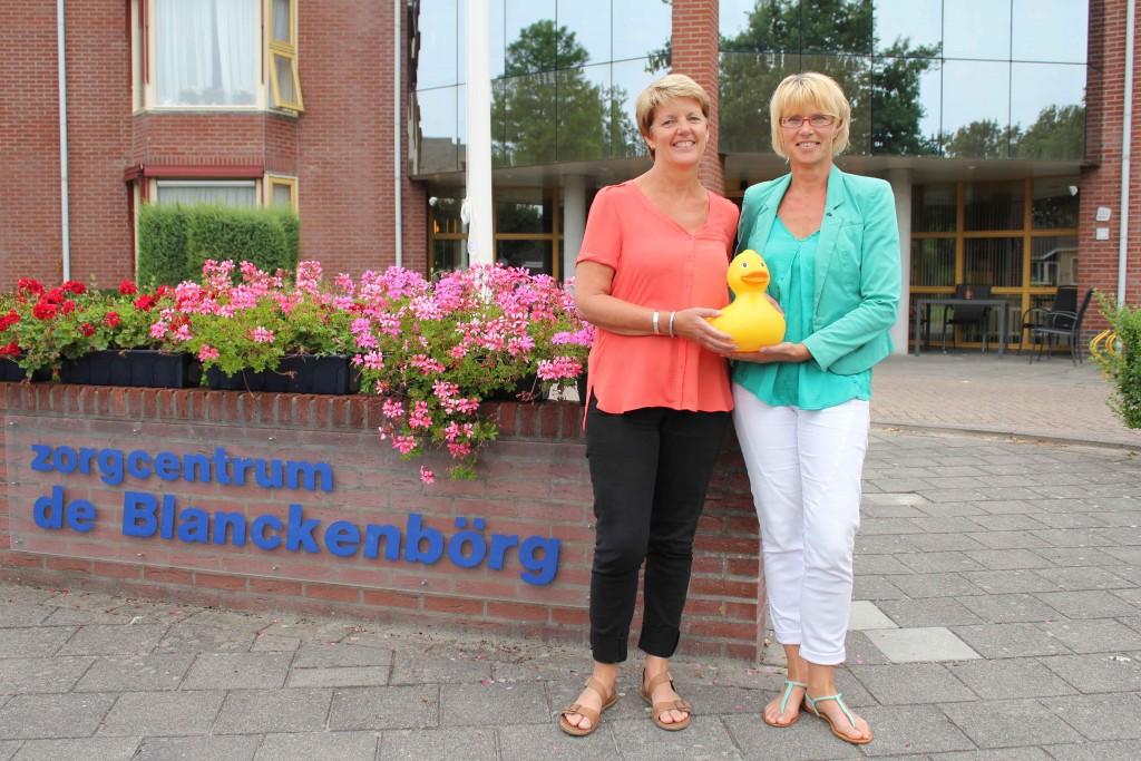 Teamleiders Clarie de ~Boer en Henny Snoek van De Blanckenborg tonen mascotte Blanckie van de Badeendjesrace, die hier op vrijdag 25 september plaatsvindt ten bate van de inrichting vansociaal restaurant in zorgcentrum De Blanckenborg in Blijham.