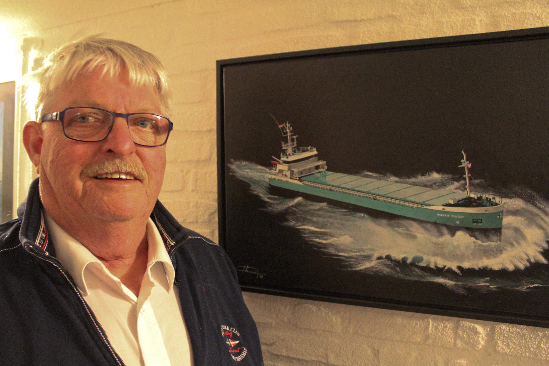 Henk Danser poseert bij zijn afscheid als kapitein en reder bij een prachtig schilderij dat hij kreeg van zijn op veel te jonge leeftijd overleden soulmate Adri Peperkamp.