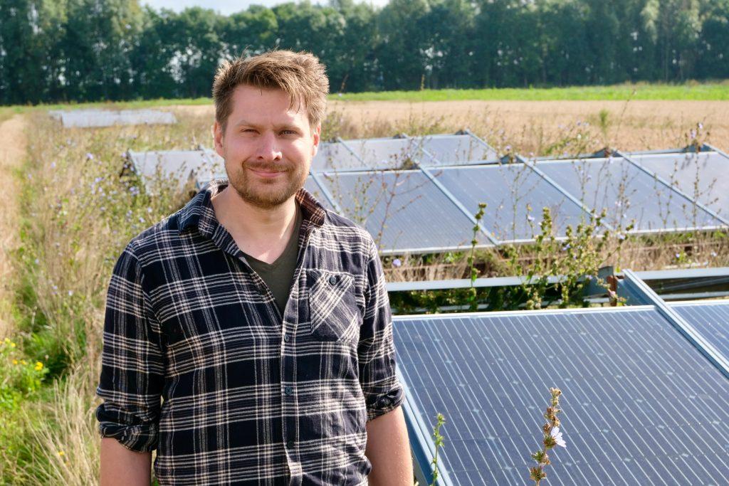 Akkerbouwer Leks Bolderdijk uit Onstwedde bij zijn mobiele zonnepanelen, een pilot voor het creëren van meer biodiversiteit (foto Jan Johan ten Have)